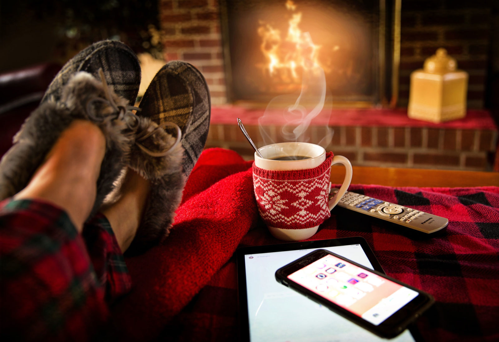 Person with slippers on with feet up in front of a fireplace with a mug of hot coco